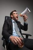 Junger Geschäftsmann, der auf Stuhl schreit und sitzt Stockfotos