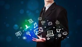 Junger Geschäftsmann, der bunte glühende Social Media-Ikonen darstellt Stockfotografie