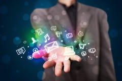 Junger Geschäftsmann, der bunte glühende Social Media-Ikonen darstellt Lizenzfreie Stockbilder