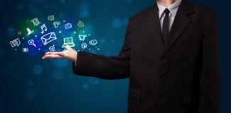 Junger Geschäftsmann, der bunte glühende Social Media-Ikonen darstellt Stockbild