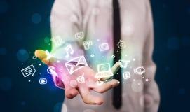Junger Geschäftsmann, der bunte glühende Social Media-Ikonen darstellt Stockfoto