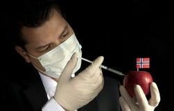 Junger Geschäftsmann, der Chemikalien in einen Apfel mit Norwegi einspritzt Lizenzfreie Stockfotos