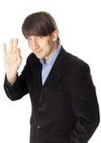 Junger Geschäftsmann, der das okayzeichen lokalisiert auf weißem backgr gestikuliert Stockfotografie