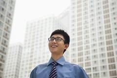 Junger Geschäftsmann, der den Himmel, draußen lächelt und betrachtet Stockfotos