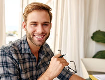 Junger Geschäftsmann, der an der Kamera bei der Arbeit lächelt Stockfoto
