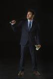 Junger Geschäftsmann, der Dollarbanknoten halten und Baseballschläger, der weg auf Schwarzem lokalisiert schaut Stockbild