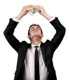 Junger Geschäftsmann, der Dollarscheine über seinem Kopf hält Lizenzfreie Stockfotografie