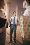 Junger Geschäftsmann, der draußen Kaffee für zwei Frauen nachts holt Lizenzfreies Stockfoto