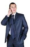 Junger Geschäftsmann, der durch Telefon spricht Stockbild