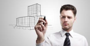 Junger Geschäftsmann, der ein Projekt des Gebäudes zeichnet stockfoto