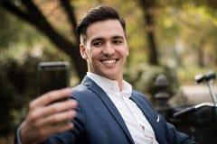 Junger Geschäftsmann, der ein selfie mit seinem Smartphone im Park nimmt lizenzfreie stockfotografie