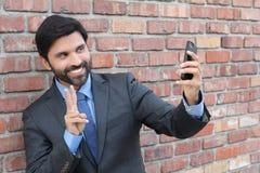 Junger Geschäftsmann, der ein selfie mit seinem Smartphone nimmt lizenzfreie stockfotos