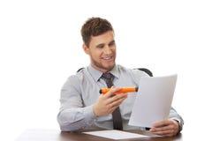 Junger Geschäftsmann, der eine Anmerkung schreibt Lizenzfreie Stockbilder