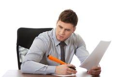 Junger Geschäftsmann, der eine Anmerkung schreibt Lizenzfreies Stockbild