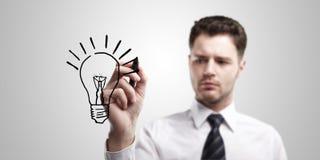 Junger Geschäftsmann, der eine Glühlampe zeichnet Lizenzfreie Stockfotos