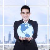 Junger Geschäftsmann, der eine Kugel hält Lizenzfreies Stockfoto