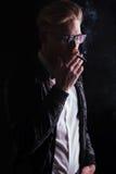 Junger Geschäftsmann, der eine Lederjacke genießt seine Zigarette trägt Lizenzfreies Stockfoto