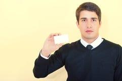 Junger Geschäftsmann, der eine unbelegte Visitenkarte zeigt stockfotografie