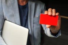Junger Geschäftsmann, der eine Visitenkarte hält Stockbilder