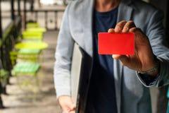Junger Geschäftsmann, der eine Visitenkarte hält Stockfotos