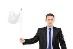 Junger Geschäftsmann, der eine weiße Flagge wellenartig bewegt Lizenzfreies Stockbild