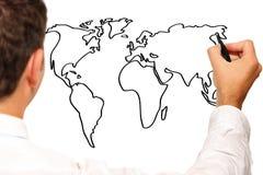 Junger Geschäftsmann, der eine Weltkarte zeichnet Lizenzfreies Stockfoto