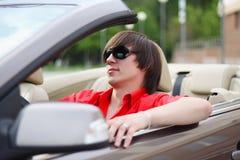 Junger Geschäftsmann, der in einem Auto sitzt Stockbilder