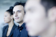Junger Geschäftsmann, der in einem Geschäftstreffen mit Kollegen sitzt Stockbilder