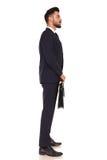 Junger Geschäftsmann, der einen Aktenkoffer und ein Schlangestehen hält stockbild