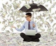 Junger Geschäftsmann, der einen Regenschirm mit Dollarregen hält Lizenzfreies Stockfoto