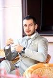 Junger Geschäftsmann, der einen Tasse Kaffee beim Sitzen trinkt Stockbilder