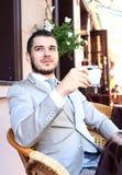 Junger Geschäftsmann, der einen Tasse Kaffee beim Sitzen trinkt Lizenzfreie Stockfotos