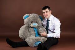 Junger Geschäftsmann, der einen Teddybären umarmt Lizenzfreie Stockfotografie