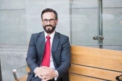 Junger Geschäftsmann, der entspannende Pause auf der Bank im Freien macht Stadt-Leben-Reihe Geschäftspersonen Porträt eines Gesch stockfotos