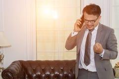 Junger Geschäftsmann, der erfolgreich am Handy in Büro w spricht stockfotos