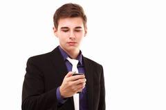 Junger Geschäftsmann, der ernsthaft zum Telefon schaut Lizenzfreie Stockfotografie