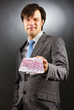 Junger Geschäftsmann, der Eurobanknoten und das Blinzeln zeigt Stockfotos