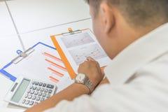 Junger Geschäftsmann, der Finanzdiagramme im Büro überprüft stockbild