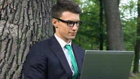 Junger Geschäftsmann, der in der Frischluft des Parks, freiberuflich tätige Beschäftigung, Freiheit arbeitet stock footage