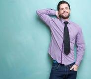 Junger Geschäftsmann, der gegen blauen Hintergrund lächelt Stockfoto