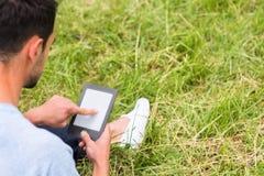 Junger Geschäftsmann, der an Gerät arbeitet und auf dem grünen Gras sitzt stockfoto