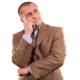 Junger Geschäftsmann, der, getrennt auf Weiß denkt Stockbilder