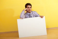 Junger Geschäftsmann, der hinter unbelegter Anschlagtafel sitzt lizenzfreies stockbild