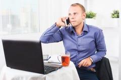 Junger Geschäftsmann, der im Büro arbeitet, an einem Tisch sitzt und am Telefon spricht Lizenzfreie Stockfotos