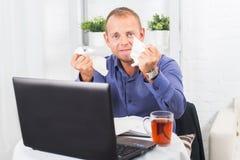Junger Geschäftsmann, der im Büro, sehr beteiligt, eine Panik, zerknittertes Papier arbeitet Lizenzfreies Stockbild