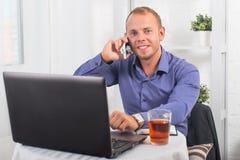 Junger Geschäftsmann, der im Büro, sitzend an a arbeitet Stockbild
