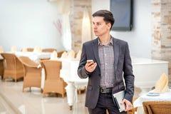 Junger Geschäftsmann, der im Büro steht Stockbild