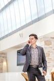 Junger Geschäftsmann, der im Büro steht und am Telefon spricht Y Lizenzfreie Stockfotos