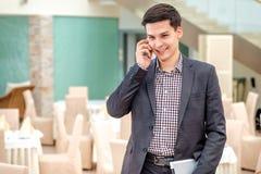 Junger Geschäftsmann, der im Büro steht und am Telefon spricht Y Stockbilder