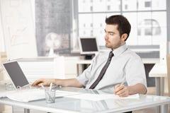 Junger Geschäftsmann, der im Büro unter Verwendung des Laptops arbeitet Stockbild